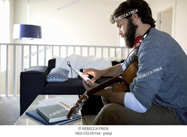 Man with guitar recording music with digital tablet