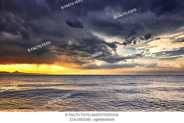 Storm clouds by sunset at the Mediterranean sea. Denia. Alicante. Valencia Community. Spain