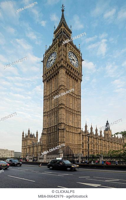 The typical black cabs on the way beside Big Ben and Westminster Palace London United Kingdom