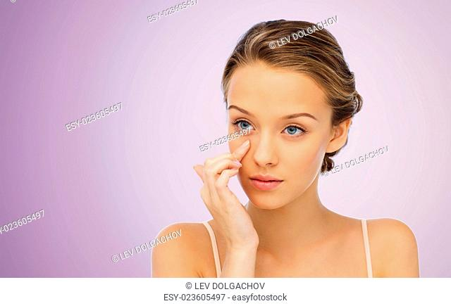 beauty, people, cosmetics, skincare and health concept - young woman applying cream to her face over violet background