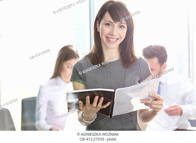Portrait smiling businesswoman holding report