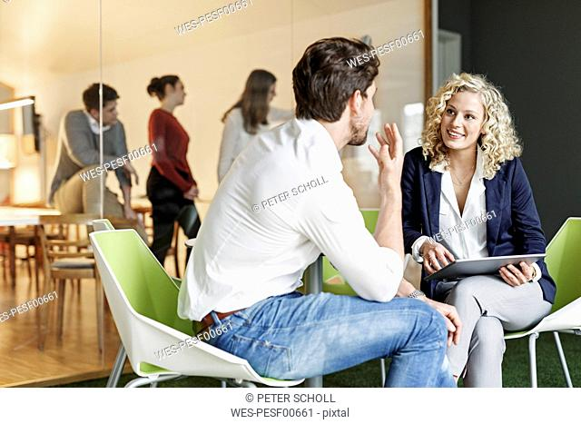 Two colleagues talking in office with meeting in background