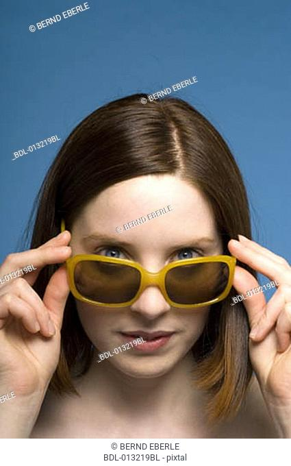 young woman looking over her sunglasses