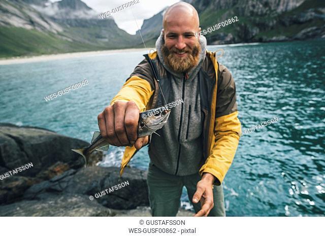 Norway, Lofoten, Moskenesoy, Young man holding freshly caught fish