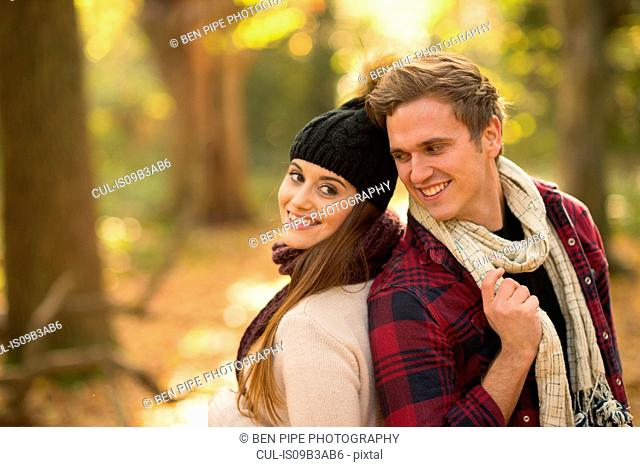 Young couple in forest, back to back, smiling