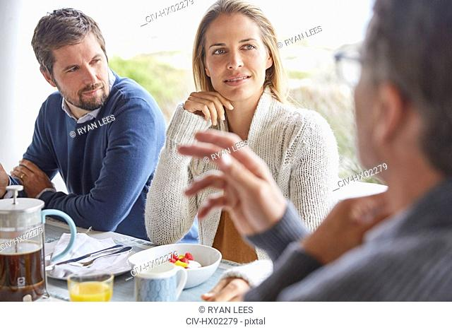 Family enjoying breakfast talking on patio