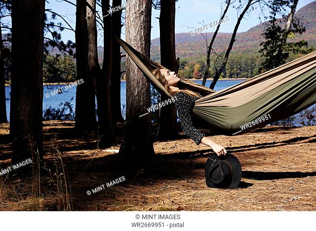 A woman lying in a hammock relaxing, under the pine trees by a lake