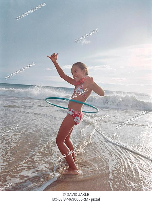 Girl hula hooping in waves on beach