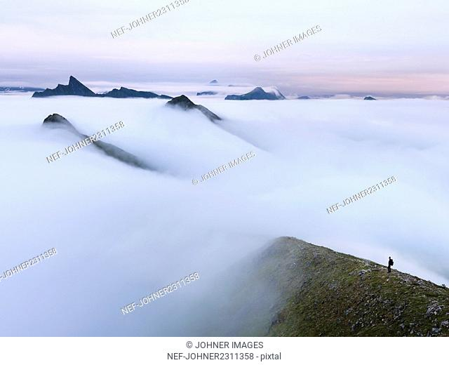 Man in foggy mountain landscape at sunrise