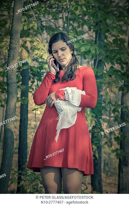 Young woman in a red dress in the woods during autumn, holding a shawl and talking on her cell phone