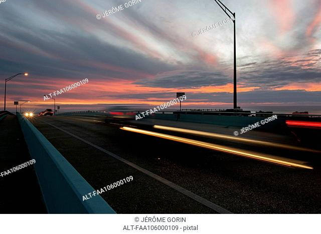 Light trails from traffic on highway at sunset