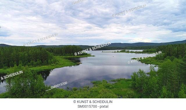 Clouds are reflected in the glassy water of a forest lake on a summer day in northern Sweden