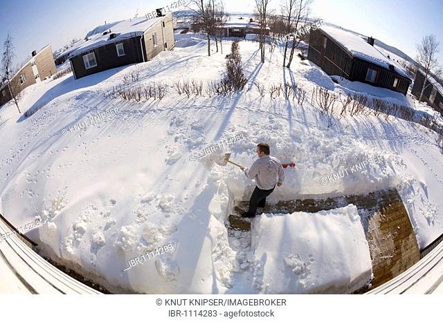 Man clearing the snow from the terrace of hid garden, Kiruna, Lappland, Northern Sweden