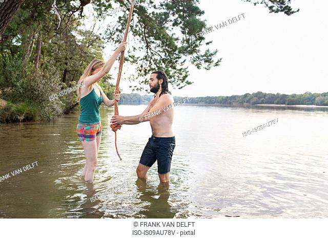 Young couple rope swinging above lake