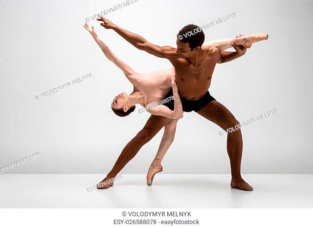 Couple of ballet dancers dancing over gray background