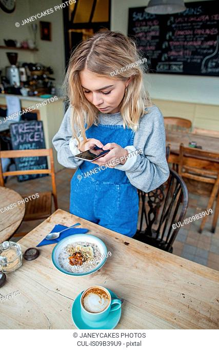 Young woman in cafe, using smartphone