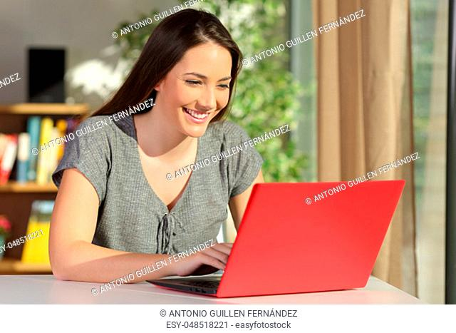 Casual single beautiful and happy housewife writing an e mail on line in a red laptop sitting in a table at home