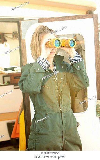 Woman looking through binoculars on boat deck