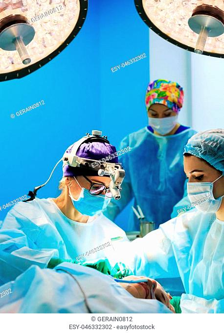 Surgery, medicine and people concept - surgeons in operating room at hospital during their work