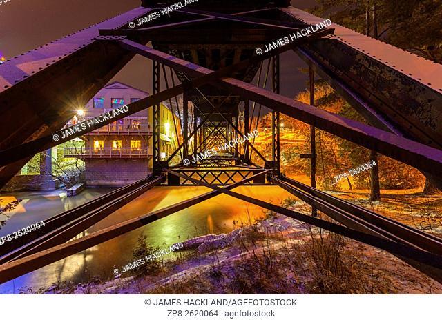 Underneath a pratt truss rail bridge spanning the Muskoka River. Bracebridge, Muskoka, Ontario, Canada