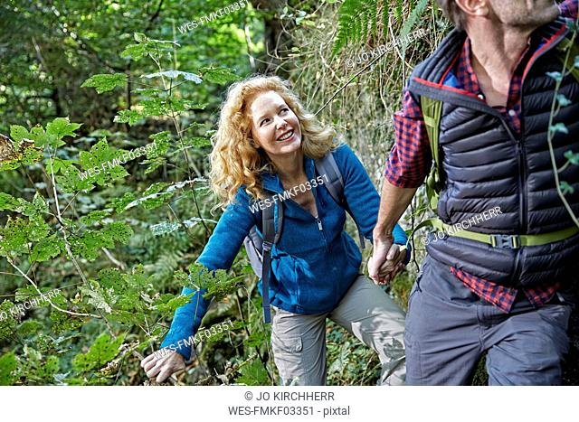 Couple hiking in forest, holding hands