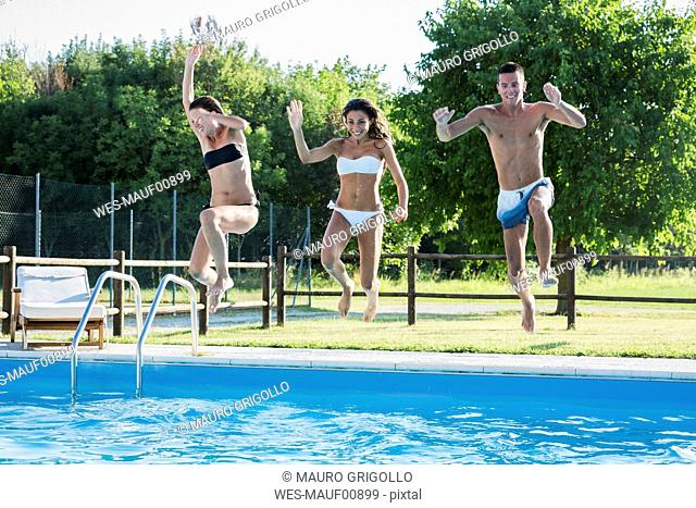 Three friends relaxing at pool edge