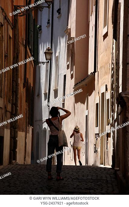 young woman tourist taking photograph in street road in the Santa Angelo district near the Jewish ghetto in Rome, Italy
