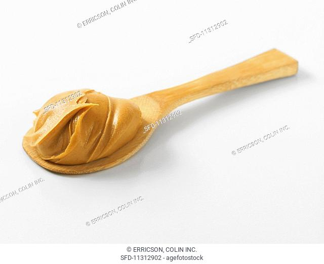 A dollop of peanut butter on a wooden spoon