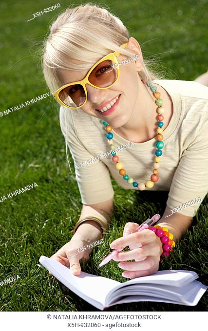 one young woman reading book on the grass in summer