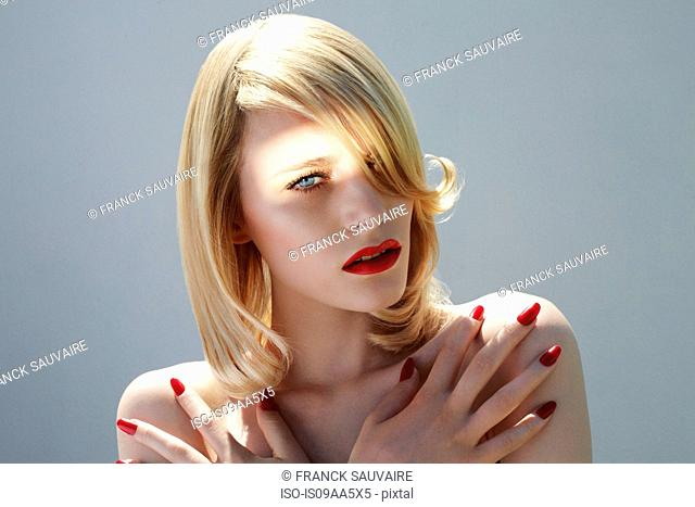 Young woman with red fingernails, portrait