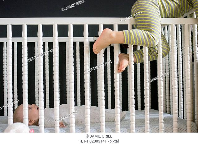 Girl (2-3) climbing on crib and brother (6-11 months) lying inside