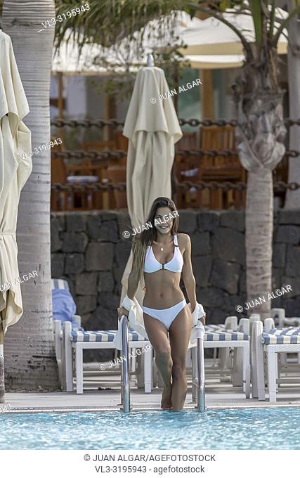 Beautiful content woman in white bikini walking into refreshing water of pool of resort smiling at camera