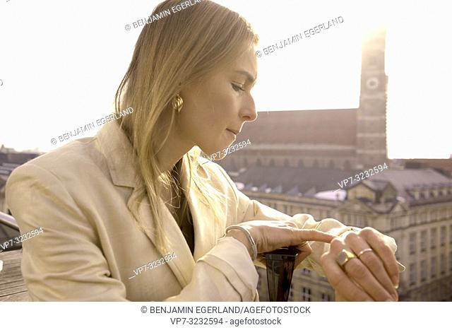 fancy blogger woman checking time of wristband on balcony next to church Frauenkirche, Marienkirche, in city Munich, Bavaria, Germany