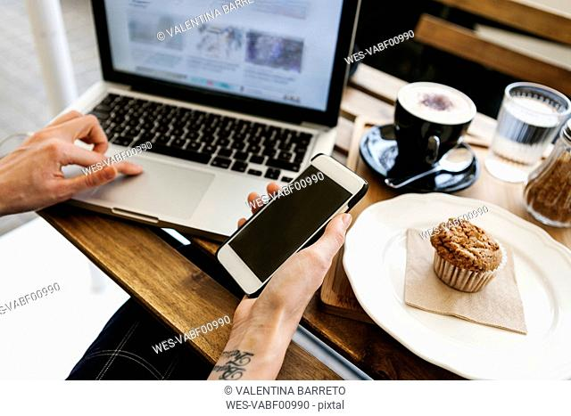 Young woman working with laptop in a street cafe, partial view