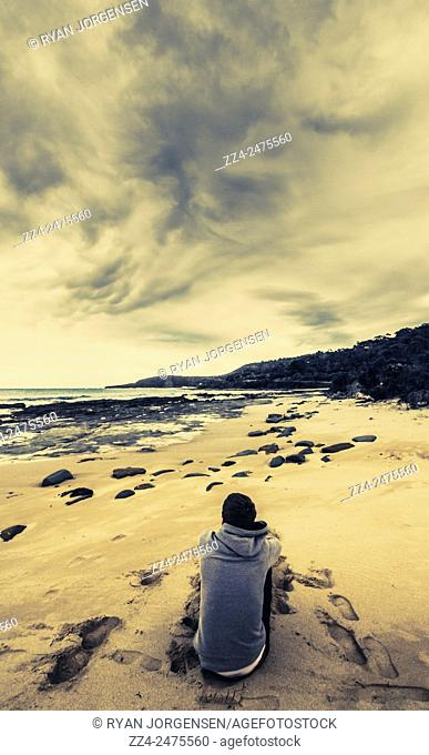 Rear view of a young man sitting dreaming and contemplating the scenery on a white sand beach during sunset, Point Hawdon Beach, Great Ocean Road, Victoria