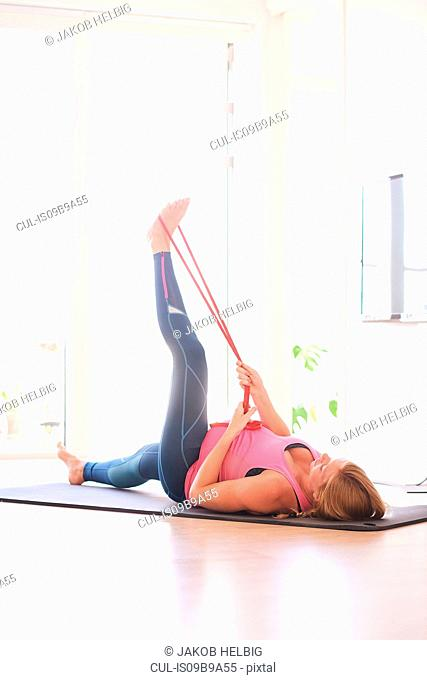 Pregnant young woman doing exercise in living room raising her leg