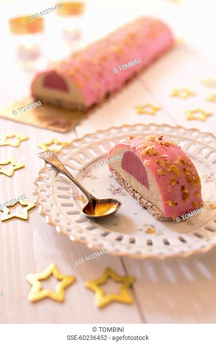 Vanilla-raspberry Chritmas log cake coated with pink icing