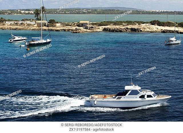 Sa Sequi Restaurant, Cala Savina beach, Formentera island, Balears Islands, Spain. Mediterranean food. A yacht sailing