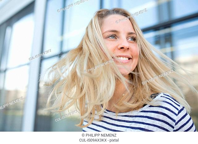 Portrait of young woman outdoors, smiling
