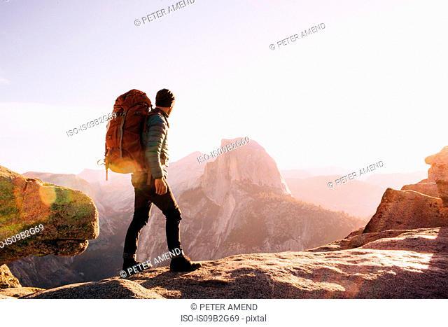 Hiker walking on mountain path, Yosemite, California, USA