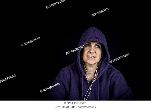 A portrait of a woman wearing a hoodie with a black background