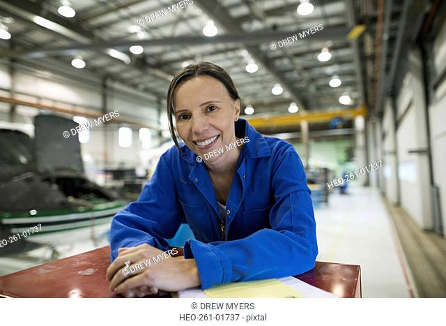 Portrait smiling female helicopter mechanic in airplane hangar