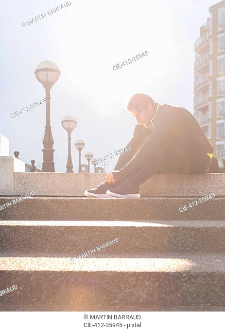 Male runner tying shoes on sunny urban stairs