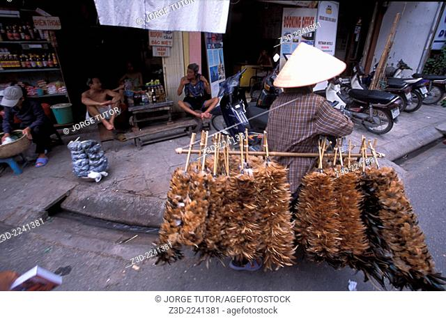 Feather dustor vendor walking the streets of Hanoi with her Non la palm-leaf conical hat
