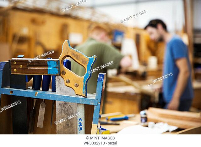 Close up of hand tools in boat-builder's workshop, two men working in background