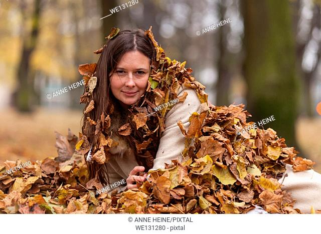 Woman appearing out of heap of leaves