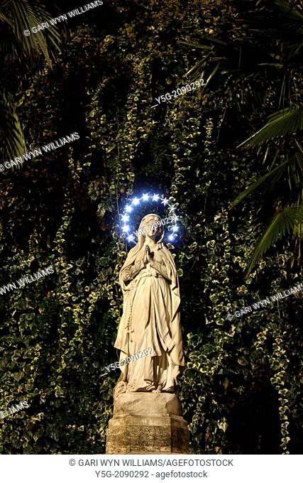 praying virgin mary statue at night outside church in rome in italy