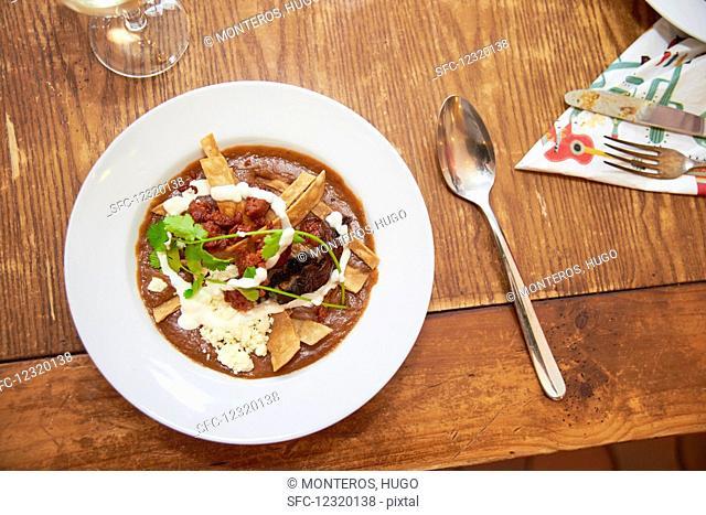 Creamy bean soup with fried tortilla strips, chorizo, chilli rings, sour cream, feta and coriander (Mexico)
