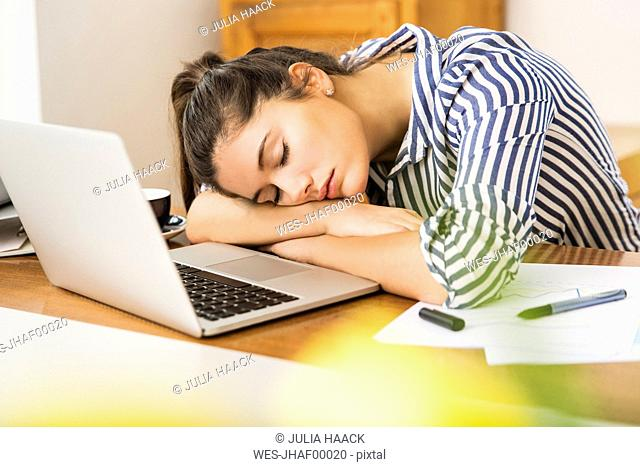 Young woman sleeping in front of her laptop at home
