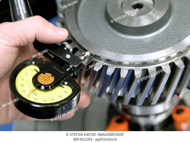 An employee of the Heidelberger Druckmaschinen AG checking the axial and radial runout of a gear with a dial gauge, in the manufacture of offset-printing...